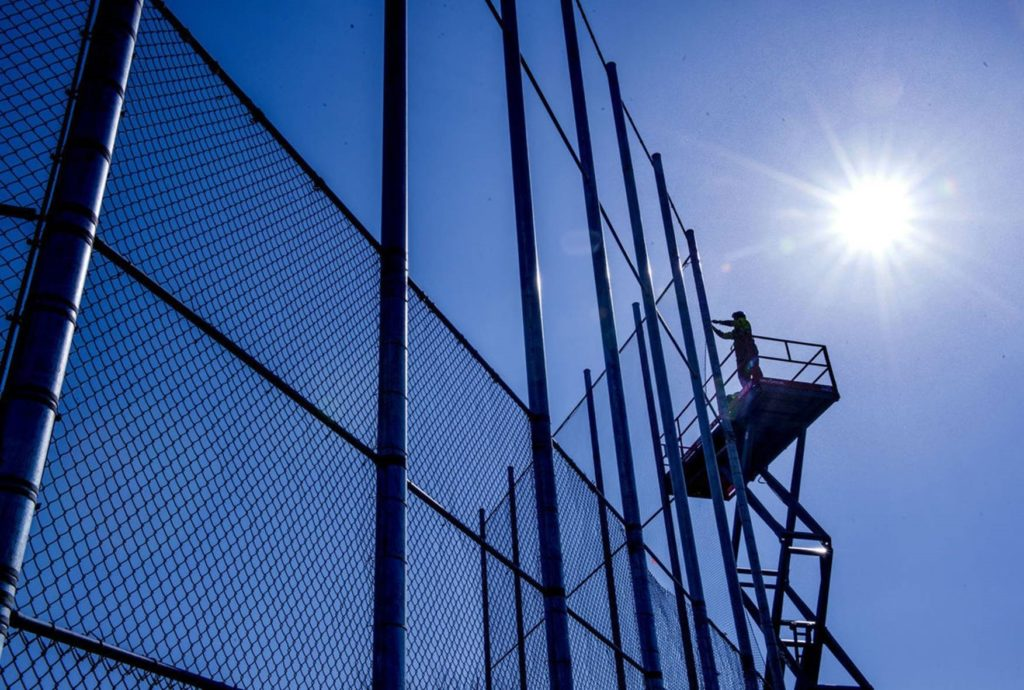 American Fence Company worker on a lift installing chain link fabric on a 40 foot backstop with the sun shining behind him