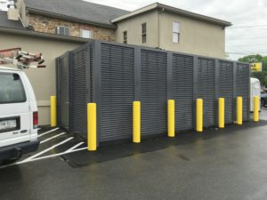 Mission Dispensary featuring dark gray PalmSHIELD louvered mechanical equipment screening with bright yellow traffic columns installed along the perimeter for protection