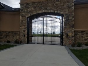 Arched ornamental double swing gates with decorative pickets and finials