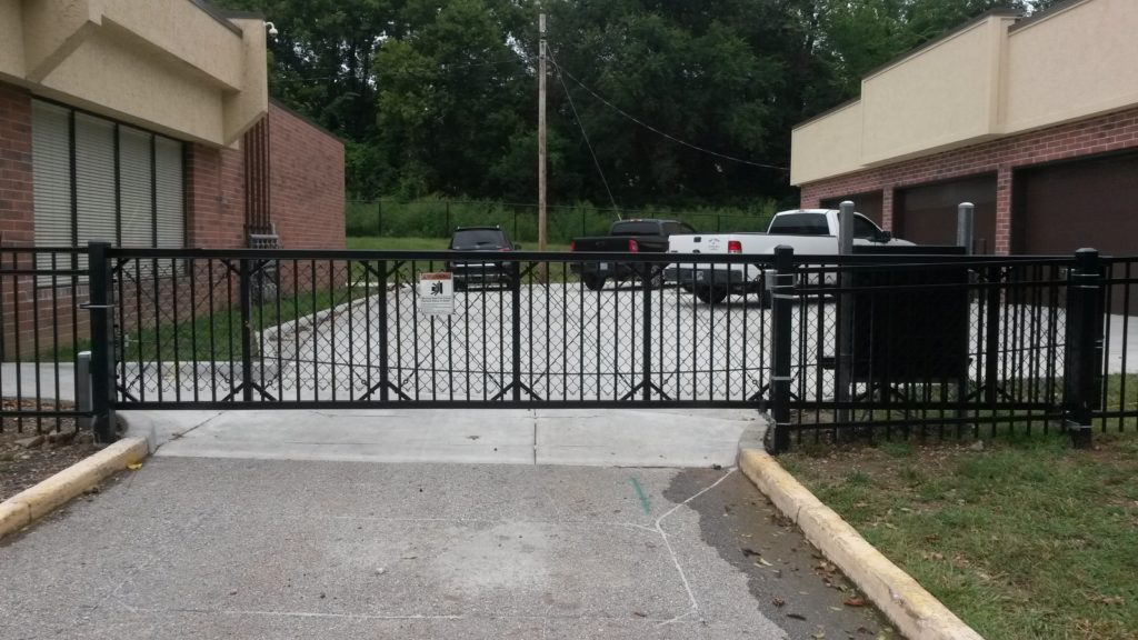 Automated ornamental cantilever gate with vertical pickets and chain link mesh