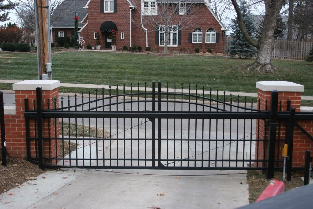 Residential ornamental cantilever estate gate between two brick pillars