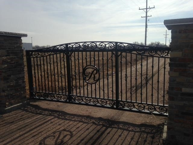 "Decorative cantilever gate installed in front of a driveway with intricate scroll work and a custom ""R"" in the middle"