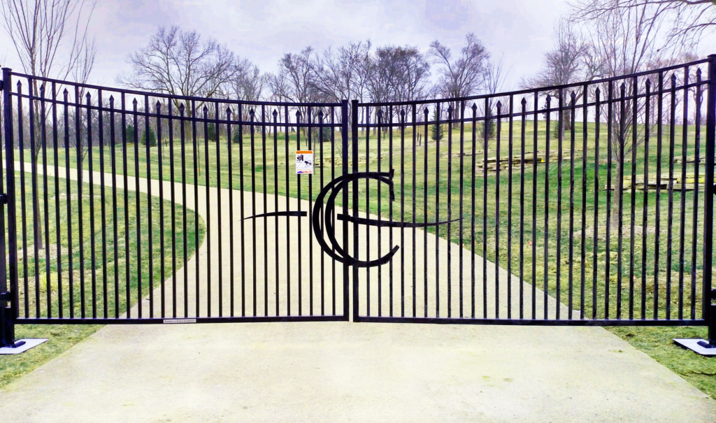 """Black double swing under arch ornamental residential gate with """"C"""" emblem in the middle"""