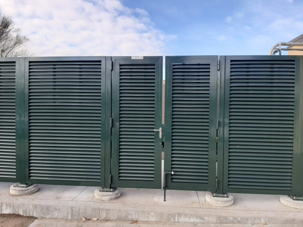 Green powder coated louvered commercial swing gates installed on top of concrete