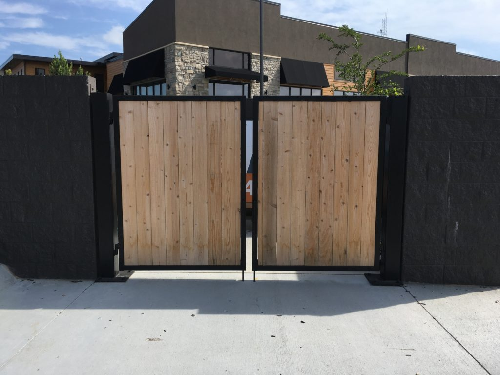 Commercial swing gates with a black powder coated aluminum frame and solid composite infill