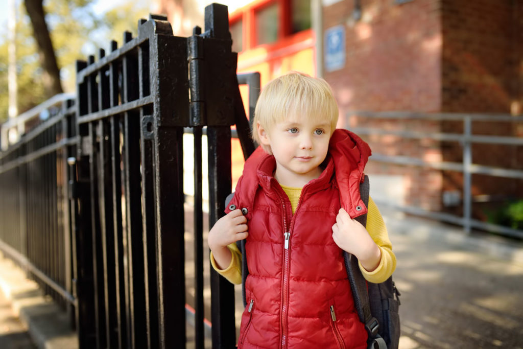 Young blonde-haired boy next to a school gate.