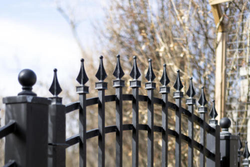 Black iron residential swing gate closeup