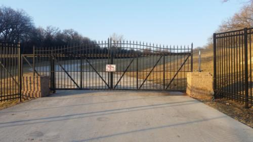 Black ornamental aluminum industrial sliding gate in front of a road entrance