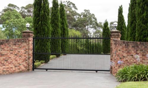 Black metal driveway entrance gates in brick fence