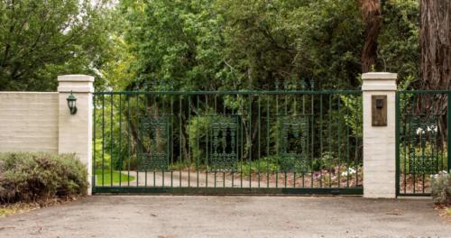 Green metal driveway entrance gates set in brick fence