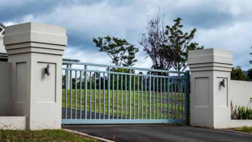 Metal driveway private residence property entrance gates set in brick fence with garden trees in background