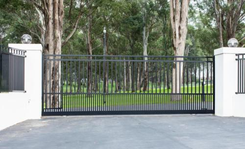 Metal driveway rural property entrance gates set in brick fence with lights and eucalyptus gum trees in background