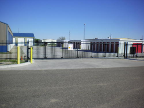 Spear top commercial cantilever gate installed in front of a storage facility
